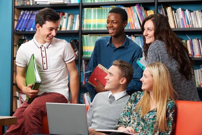 Grupp av tonårs- studenter som tillsammans arbetar i arkiv arkivfoto