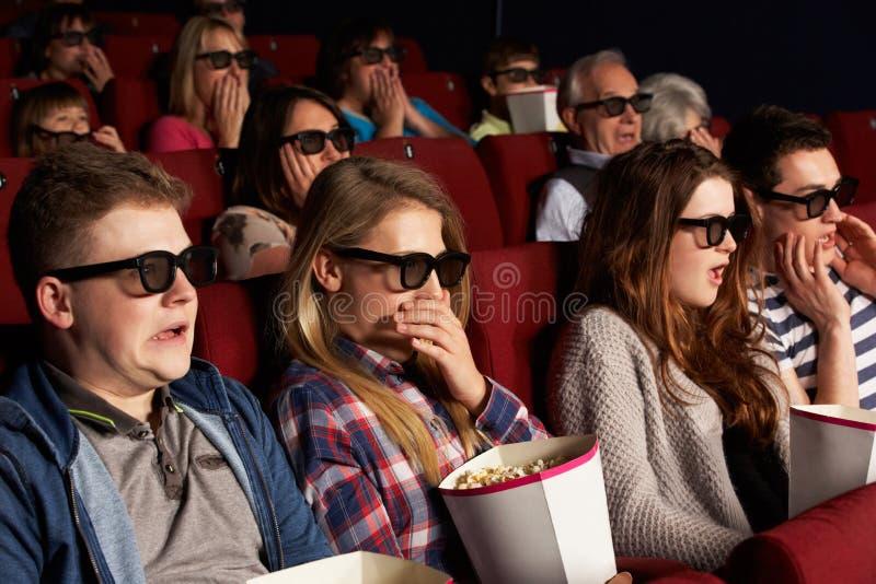 Grupp av tonårs- vänner som håller ögonen på filmen 3D fotografering för bildbyråer