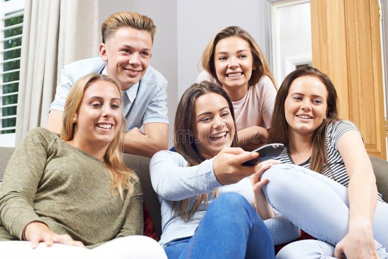 Grupp av tonårs- vänner som hemma håller ögonen på television royaltyfria bilder