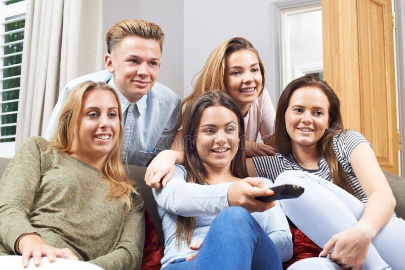 Grupp av tonårs- vänner som hemma håller ögonen på television arkivfoton