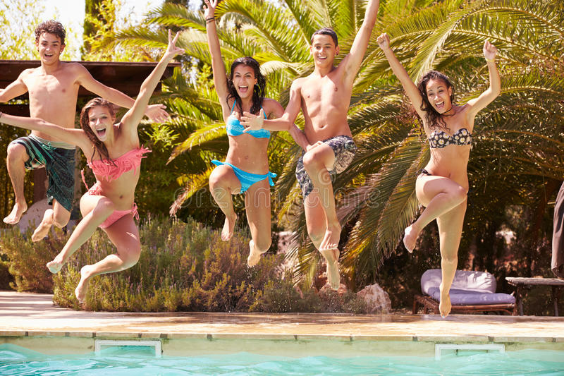 Grupp av tonårs- vänner som hoppar in i simbassäng royaltyfri foto