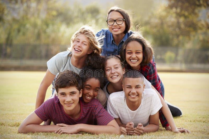 Grupp av tonårs- vänner som ligger i en hög på gräs fotografering för bildbyråer