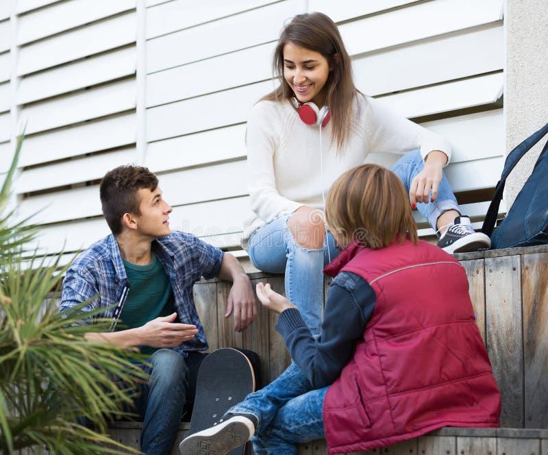Grupp av tonårs- vänner som pratar och har gyckel royaltyfria bilder