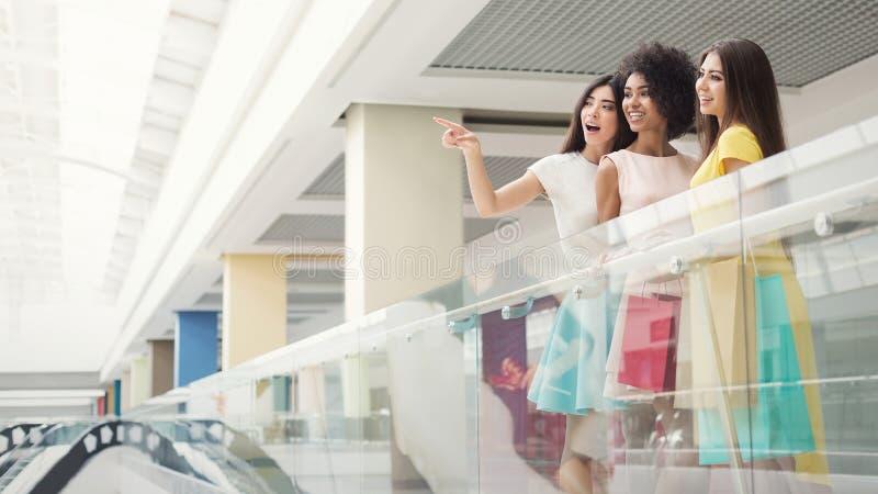 Grupp av tre flickor som tillsammans shoppar i galleria royaltyfria bilder