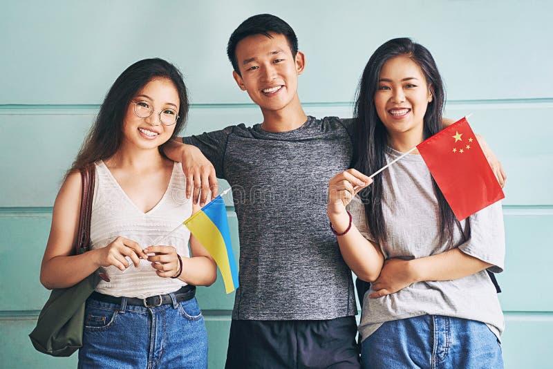 Grupp av tre glada internationella kinesiska asiatiska studenter som leker och för kinesiska och ukrainska flagg vid universitet arkivfoton