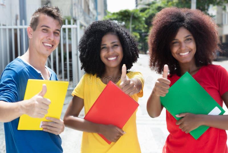 Grupp av tre internationella studenter som visar upp tummar royaltyfri fotografi