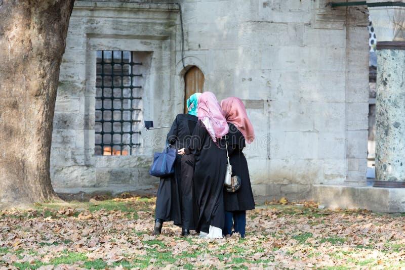 Grupp av tre islamiska klädda damer som gör självståendefotoet royaltyfri fotografi