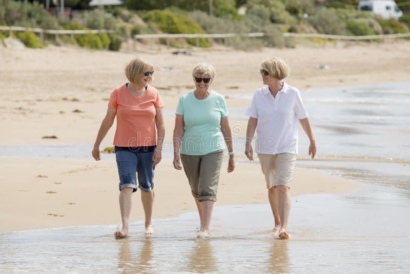 Grupp av tre mogna pensionerade kvinnor för pensionär på deras 60-tal som har gyckel som tillsammans tycker om lyckligt gå på le  fotografering för bildbyråer