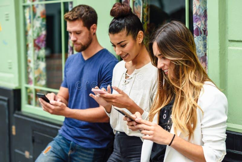 Grupp av tre personer som ner ser på smart le för telefon arkivbilder