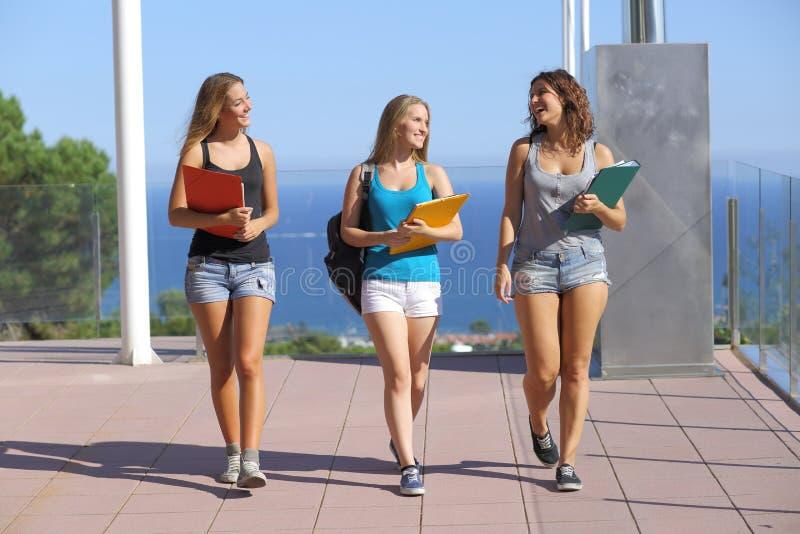 Grupp av tre studenttonåringar som går in mot kamera arkivbild