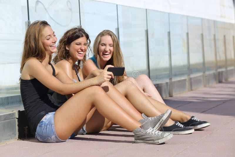 Grupp av tre tonåringflickor som skrattar, medan hålla ögonen på den smarta telefonen royaltyfri foto
