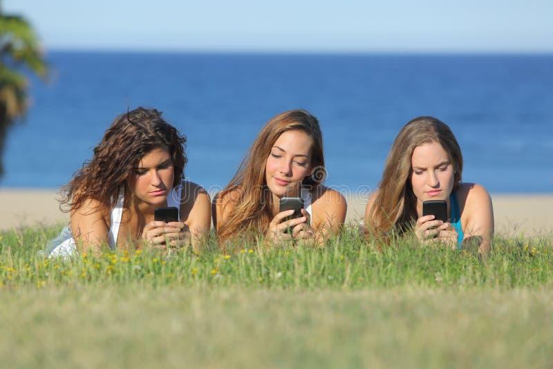 Grupp av tre tonåringflickor som skriver på mobiltelefonen som ligger på gräset royaltyfria bilder