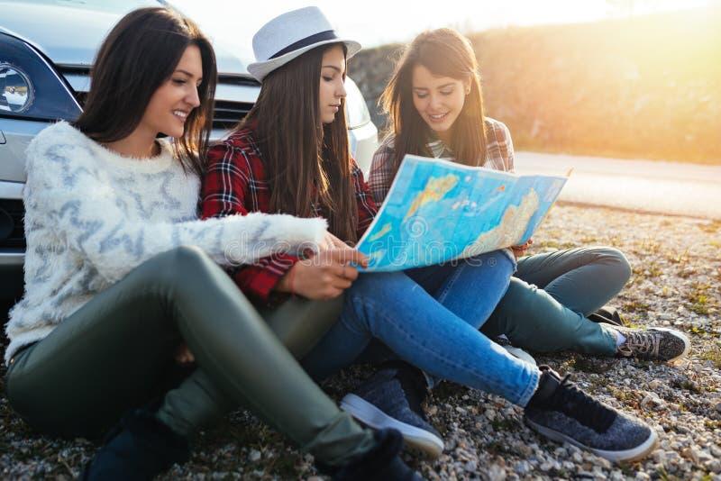Grupp av tre unga kvinnor som tillsammans reser royaltyfri bild