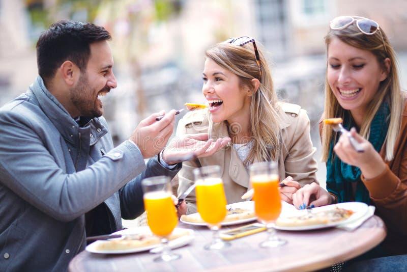 Grupp av tre vänner som äter pizza i utomhus- kafé på solig dag arkivfoto