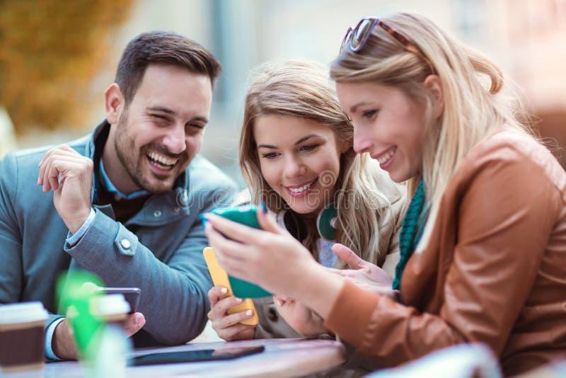 Grupp av tre vänner som använder den utomhus- digitala minnestavlan fotografering för bildbyråer