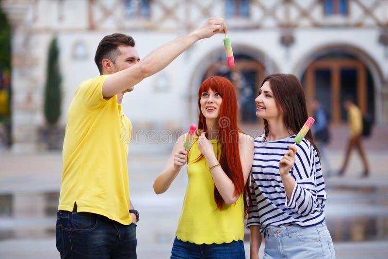 Grupp av tre vänner som går i staden som äter glass, jok royaltyfri foto