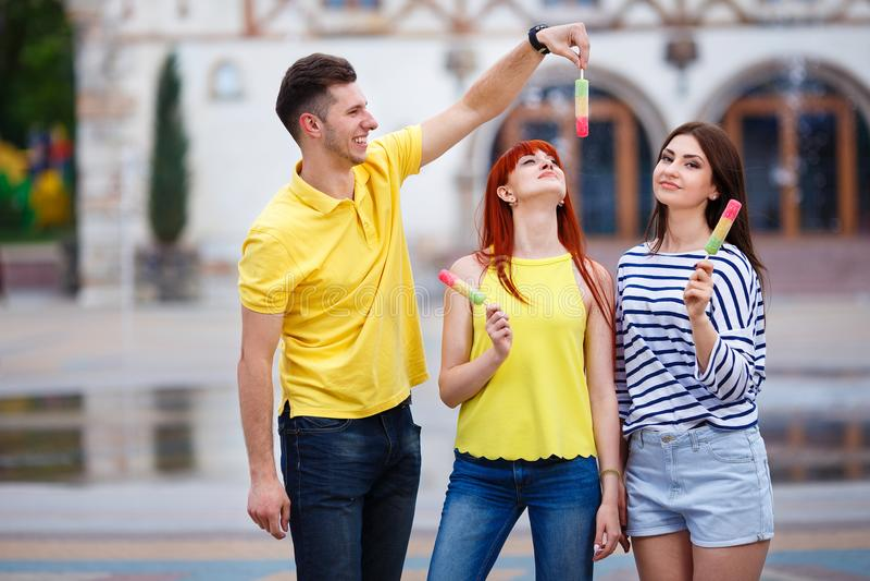 Grupp av tre vänner som går i staden som äter glass, jok fotografering för bildbyråer