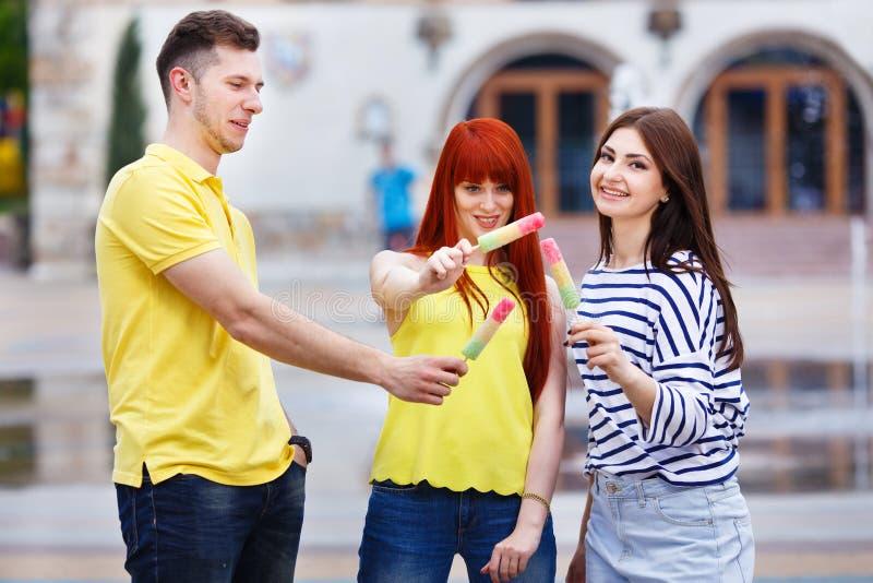 Grupp av tre vänner som går i staden som äter glass, jok royaltyfria foton