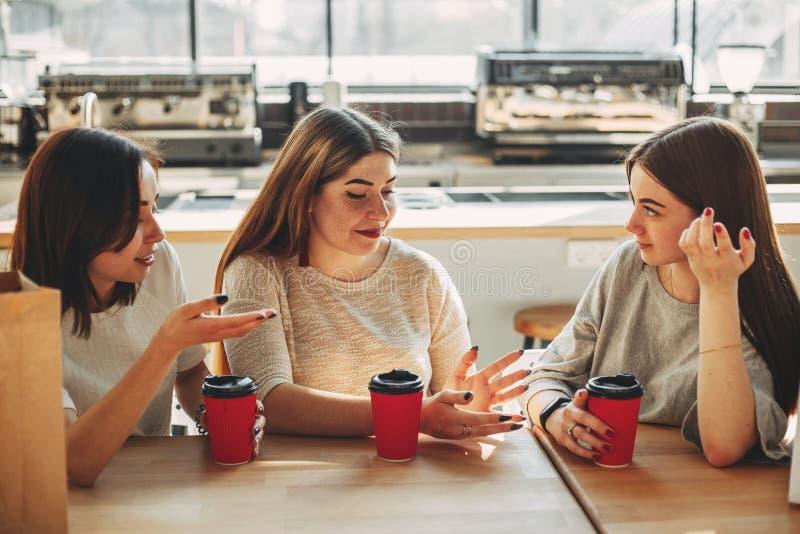 Grupp av tre vänner som har gyckel ett kaffe tillsammans Unga kvinnor arkivbilder