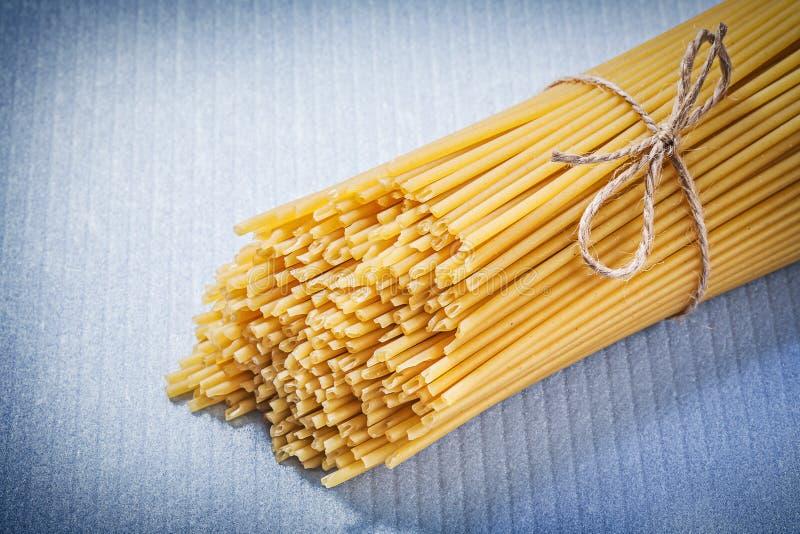 Grupp av tunn spagetti på blå bakgrundsmat- och drinkconcep arkivfoton