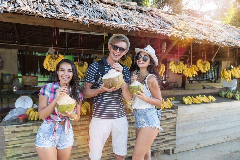 Grupp av turister som in dricker kokosnöten på Thailand gatamarknad, gladlynt man och kvinnor i traditionell fruktbasar arkivfoto