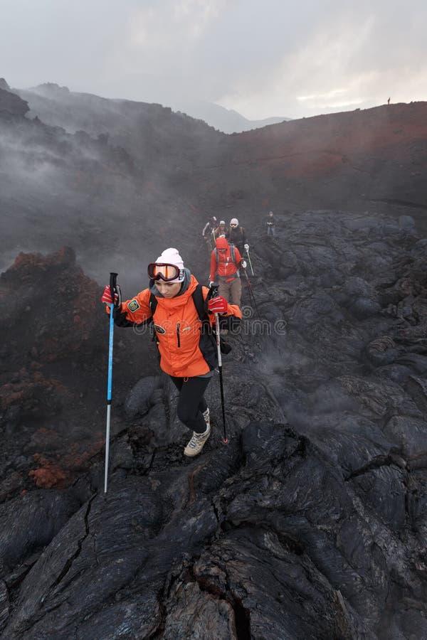 Grupp av turister som fotvandrar på den nya Tolbachik för utbrott för lavafält vulkan på Kamchatka Ryssland Far East arkivfoto