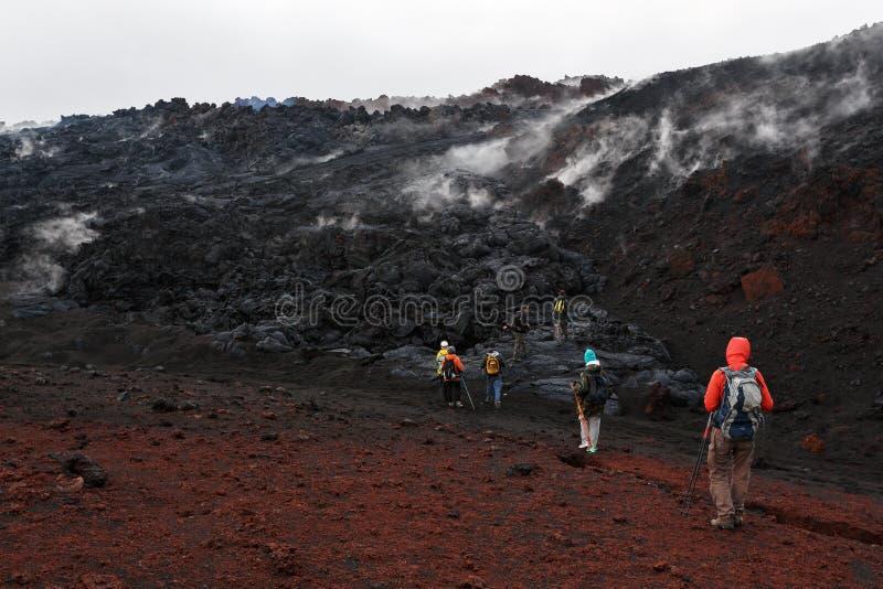 Grupp av turister som fotvandrar på den Tolbachik för utbrott för lavafält vulkan på Kamchatka Ryssland arkivbilder