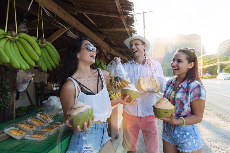 Grupp av turister som talar som dricker kokosnöten på Thailand gatamarknad, gladlynt man och kvinnor i traditionella frukter royaltyfri fotografi