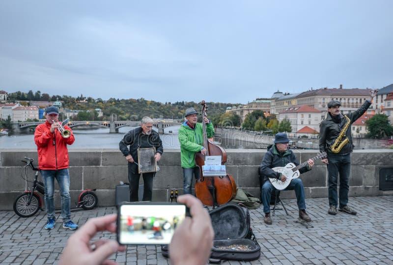 Grupp av turister som tar fotoet av musicants på den Charles bron, Prague, Tjeckien royaltyfri bild