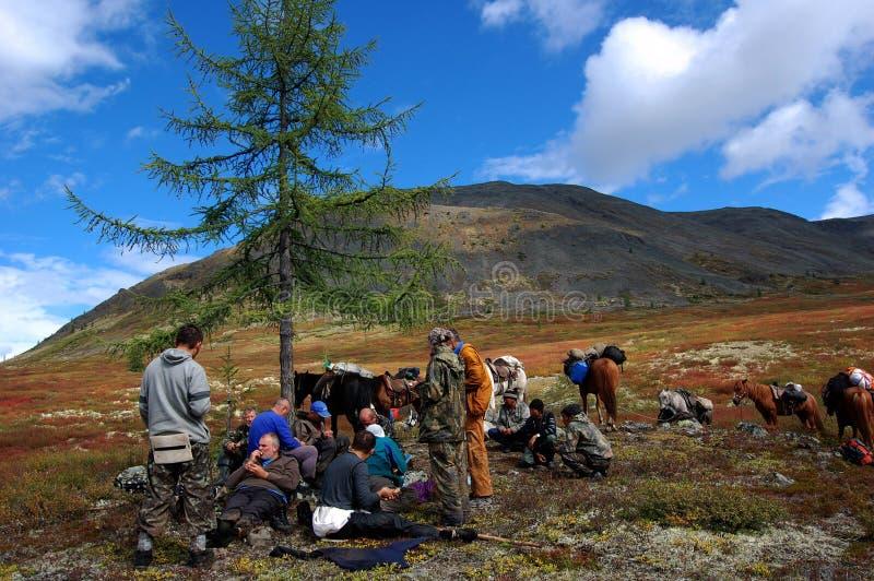 Grupp av turister som vilar på bergpasserandet arkivbild