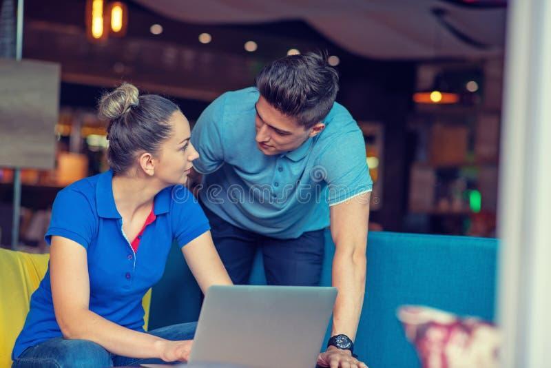 Grupp av två coworkers som arbetar jämföra beräkningdiagram i en coffee shop royaltyfri foto
