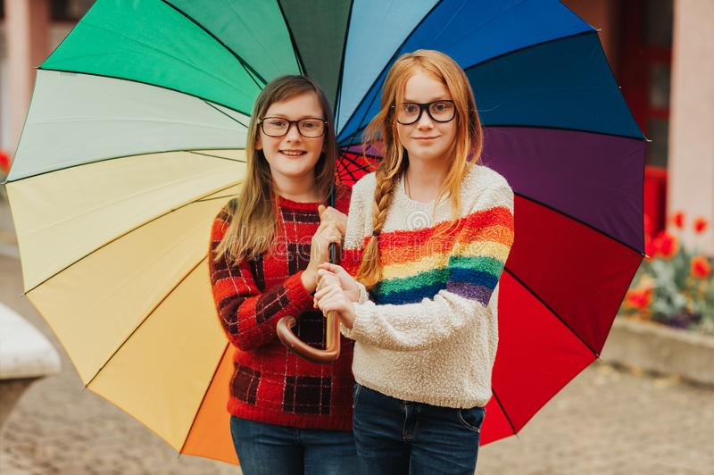 Grupp av två gulliga små flickor som spelar utanför under det stora färgrika paraplyet royaltyfri bild