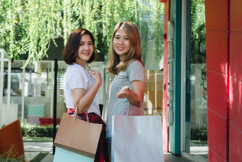 Grupp av ung asiatisk kvinnashopping i en utomhus- marknad med shoppingpåsar i deras händer royaltyfria foton