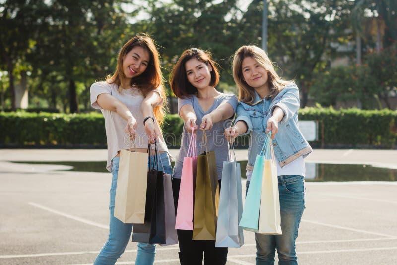 Grupp av ung asiatisk kvinnashopping i en utomhus- marknad med shoppingpåsar i deras händer royaltyfri bild