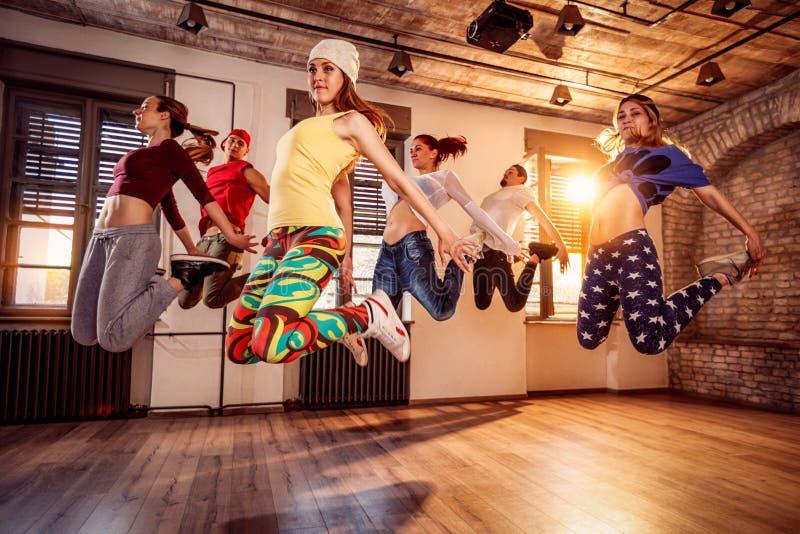 Grupp av ung dansarebanhoppning under musik royaltyfri foto