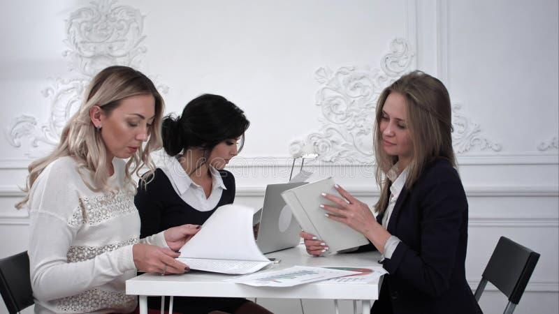 Grupp av unga affärskvinnor som arbetar med minnestavlan i ett möte på kontoret arkivfoto