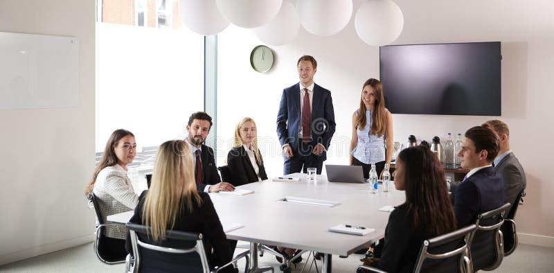 Grupp av unga affärsmän och affärskvinnor som möter runt om tabellen på den doktorand- rekryteringbedömningdagen royaltyfri fotografi