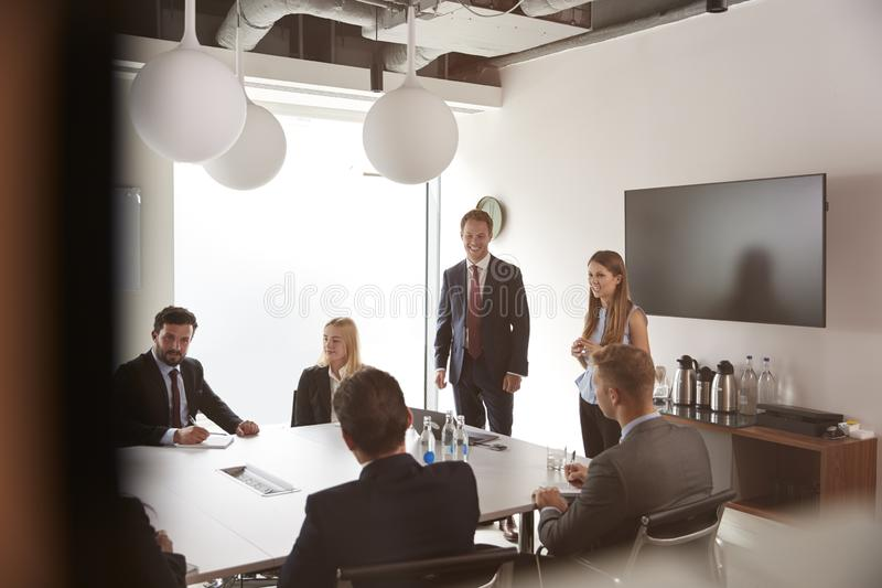 Grupp av unga affärsmän och affärskvinnor som möter runt om tabellen på den doktorand- rekryteringbedömningdagen arkivbild