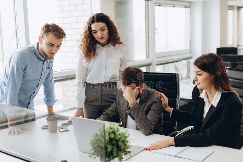 Grupp av unga affärspartners som arbetar i modernt kontor Coworkers som har problem, medan arbeta på bärbara datorn royaltyfri foto