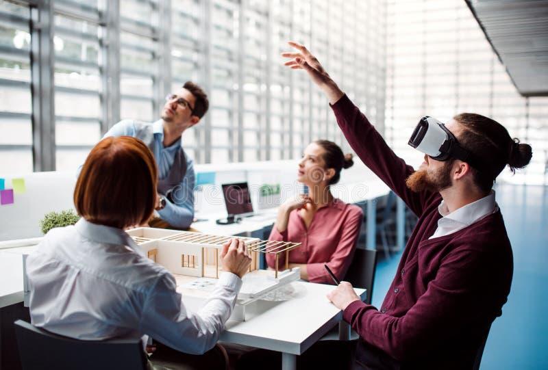 Grupp av unga arkitekter med modellen av ett hus och VR-skyddsglasögon som i regeringsställning arbetar royaltyfri foto