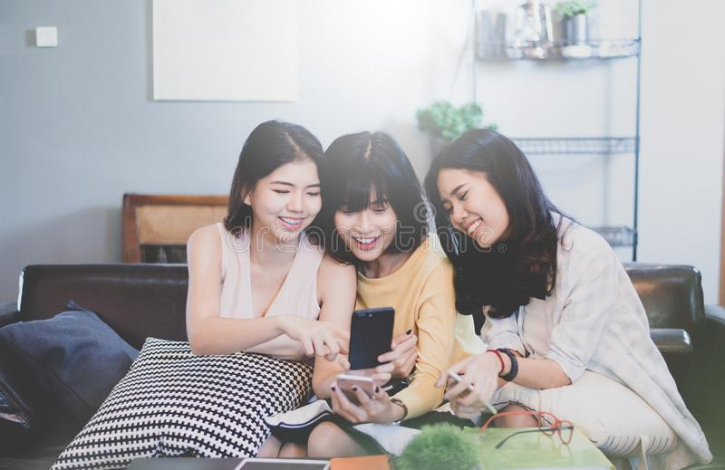 Grupp av unga asiatiska kvinnliga vänner i coffee shop, genom att använda digitala apparater som pratar med smartphones arkivfoton
