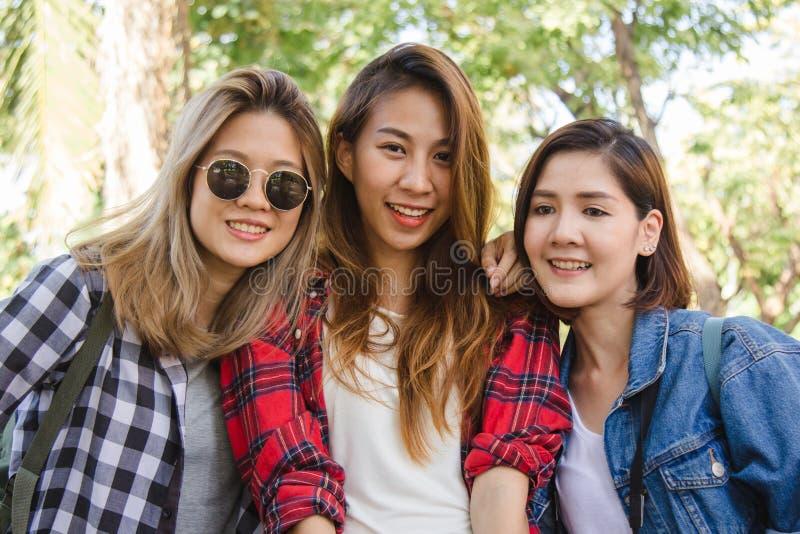 Grupp av unga asiatiska kvinnor som sitter längs gatan som tycker om deras stadslivsstil i en morgon royaltyfri foto