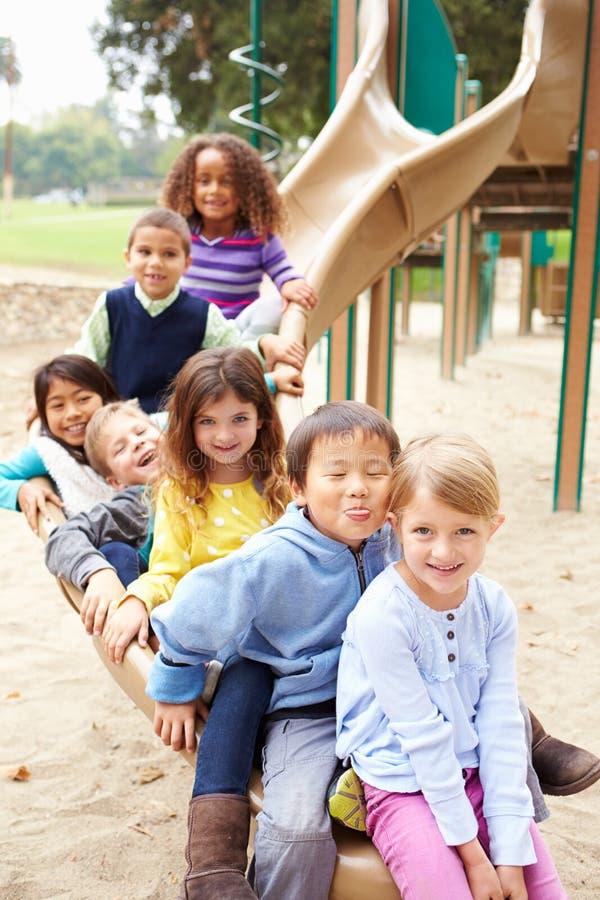 Grupp av unga barn som sitter på glidbana i lekplats royaltyfria foton