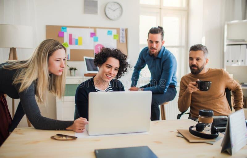 Grupp av unga businesspeople med bärbara datorn som har möte i ett modernt kontor royaltyfri bild