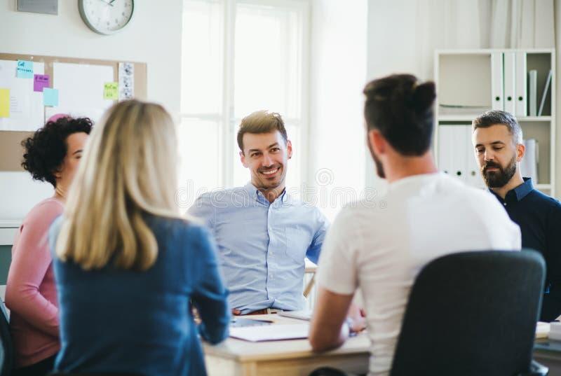 Grupp av unga businesspeople som sitter runt om tabellen i ett modernt kontor och att ha möte fotografering för bildbyråer