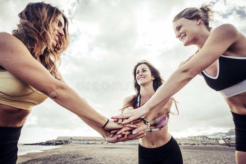 Grupp av unga caucasian riends f?r kvinnlig som tillsammans s?tter deras h?nder p? stranden klart att starta med en kondition?vni royaltyfria bilder