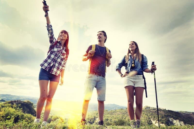 Grupp av unga fotvandrare som går in mot horisonten royaltyfri foto