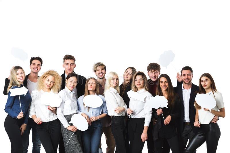 Grupp av unga härliga kvinnor och män i tillfälliga kläder med moln av tankeetiketter i händer som isoleras på vit bakgrund royaltyfria foton
