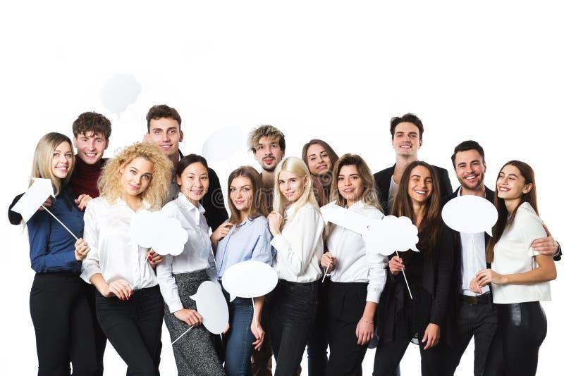 Grupp av unga härliga kvinnor och män i tillfälliga kläder med moln av tankeetiketter i händer som isoleras på vit bakgrund arkivfoton