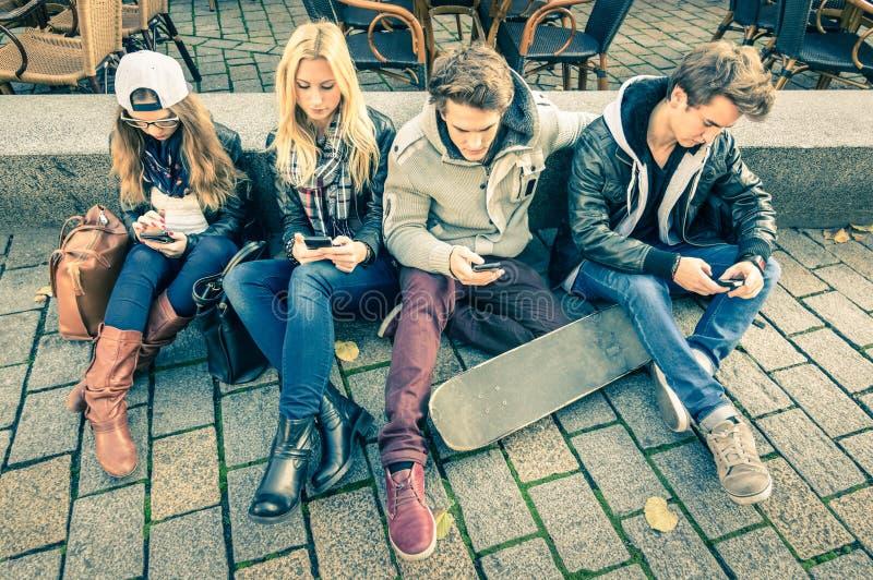 Grupp av unga hipstervänner som spelar med smartphonen fotografering för bildbyråer
